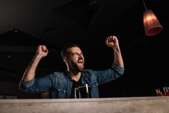 Visitor screaming at bar counter and showing yes gesture while watching royalty free stock photography