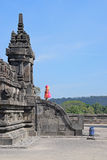 A visitor standing in front of a Temple admired by the architecture. A visitor clad in colourful dress standing in front of one of the Temples in Prambanan stock images