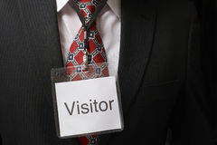 Visitor tag. Businessman wearing a visitor identification badge around his neck royalty free stock photos