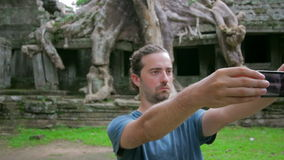 Visitor taking picture bizarre nature of preah khan temple, angkor Stock Images
