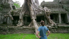 Visitor taking picture bizarre nature of preah khan temple, angkor Royalty Free Stock Image