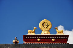 Visitor and Two golden deer flanking a Dharma Wheel. A man and the rooftop statues of two golden deer flanking a Dharma wheel on Drepung Monastery main building royalty free stock photo