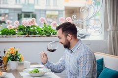 Visitor with wine glass in restaurant. The man is smelling red wine. tasting Royalty Free Stock Image
