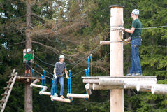 Visitors in adventure park clambering with ropes wear protective Royalty Free Stock Images