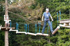 Visitors in adventure park clambering with ropes wear protective Stock Photo