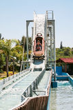 Visitors in boat on water slide attraction Stock Photo
