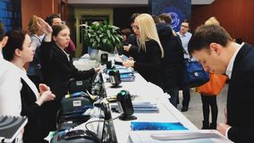 Visitors of business conference check-in in registration deck