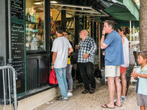 Visitors choose snacks at cafe take-away window in Jardin de Lux Royalty Free Stock Photo