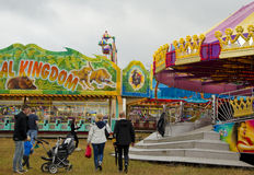 Visitors at a County fair, Sweden. Crowd of visitors at a local county fair in Sweden with with colorful amusement park rides in the background stock image