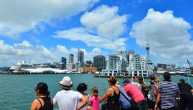 Visitors on a cruise boat looking at Auckland waterfront skyline Stock Photography