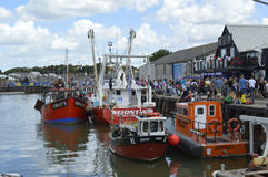 Visitors fill the harbour to sample oysters at the Whitstable Oyster Festival. WHITSTABLE, UK-JULY 22:Visitors flock to the harbour to sample oysters in the Royalty Free Stock Photos