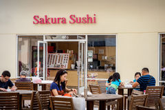 Visitors in front of Sakura Sushi. Visitors relaxing in front of Sakura Sushi at the famous Waikele Premium Outlets, Honolulu, Hawaii, USA. This venue has a Stock Photography