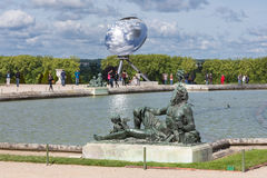 Visitors in garden Palace Versailles with statue and pond at Paris, France Royalty Free Stock Image