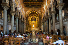 Visitors indoor of Duomo di Monreale in Sicily. MONREALE, ITALY - JUNE 25, 2011: visitors indoor of Duomo di Monreale in Sicily. The cathedral of Monreale is one royalty free stock images