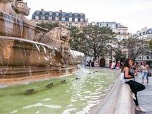 Visitors lean on lion fountain in Place Saint Sulpice, Paris Stock Photos