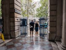 Visitors look out at rainy Strand from under Somerset House arcade. London, England, August ,23 2015: Visitors look out at rainy Strand from under Somerset House Royalty Free Stock Images