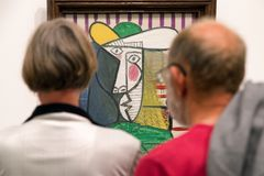 Visitors looking at Pablo Picasso painting. LONDON, UNITED KINGDOM - MAY 12: Visitors looking at Pablo Picasso painting Bust of woman at Tate modern on May 12 royalty free stock photos