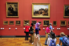Visitors at the Louvre. Tourists pause at a painting  at the Musée du Louvre, Paris, France Royalty Free Stock Images