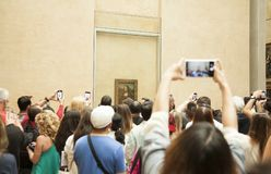 Visitors make photos of Mona Lisa painting at the Louvre Museum. PARIS, FRANCE - 11 MAY 2017: Visitors make photos of Mona Lisa painting at the Louvre Museum Royalty Free Stock Photos