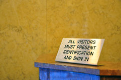 Visitors must show security identification. A shot of a sign that tells visitors must show ID to enter building Stock Image