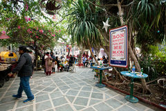 Visitors of outdoor cafe sitting under the tropical trees. Stock Photos