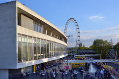 Visitors outside the Royal Festival Hall in with London Eye in t Royalty Free Stock Photo