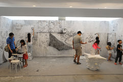 Visitors painting on a wall at the Affordable Art Fair 2017 in Singapore. Stock Image