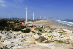 Visitors play on the sandy stone beach under wind turbine Royalty Free Stock Photography