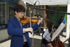 Visitors return to Marathon Place. Boston, Massachusetts USA - April 28, 2013 - Violinist plays for visitors to Marathon Place, site of one of two Marathon Stock Images