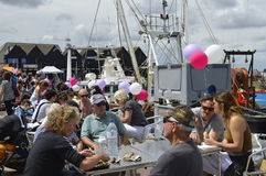 Visitors sit by the harbour to sample oysters at the Whitstable Oyster Festival. WHITSTABLE, UK-JULY 22:Visitors sitting by the harbour enjoying the oysters in Royalty Free Stock Photography