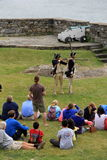 Visitors sitting or standing near young men reenacting the firing of muskets,Fort Ticonderoga,New York,2014 Royalty Free Stock Images