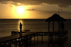 Visitors at sunset light. Peoples relaxing on a dock at sunset, near Flic an Flac at Mauritius Island Stock Photos