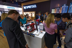 Visitors taste the coffee from the Nespresso Stock Photography
