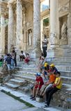 Tourists at the Library of Celsus at Ephesus in Turkey. Visitors to the ancient site of Ephesus relax in the shade on the steps of the Library of Celsus Royalty Free Stock Photography