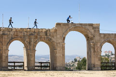 Visitors to the ancient site of Jerash in Jordan walk along the remains of the arched Hippodrome. Royalty Free Stock Images