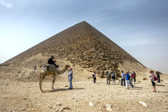 Visitors to Dahshur in northern Egypt stand beside the Red Pyramid. The Red Pyramid was built by Pharaoh Sneferu (2613 - 2589 BC) and is considered to be the Stock Image