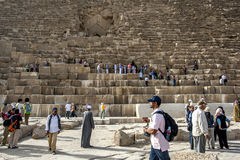 Visitors to Giza in Cairo in Egypt climb over the Pyramid of Khufu. The pyramid was constructed around 2570 BC using 2.3 million limestone blocks Royalty Free Stock Photos