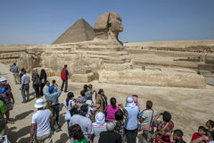 Visitors to Giza in Cairo in Egypt view the Pyramid of Khufu and the Sphinx. The Great Sphinx is a large human-headed lion that was carved from a mound of Royalty Free Stock Photos