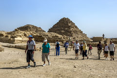 Visitors to Giza in Egypt walk past the Pyramids of the Queens Stock Photos