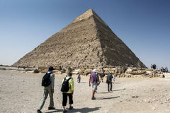 Visitors to Giza gather around the base of the Pyramid of Khafre in Cairo, Egypt. This pyramid stands 136 metres high and its peak still has the original royalty free stock images