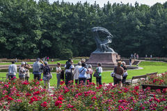 Visitors to Lazienki Park in Warsaw in Poland admire the Chopin Monument. royalty free stock images