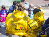 Visitors to Lego Land in the rain. Visitors keeping dry at Lego Land by wearing yellow plastic Lego Land mac Stock Images