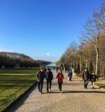 Visitors to Versailles Palace grounds bundle up for winter temperatures on a sunny afternoon Stock Photography