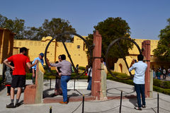 Visitors with tourist guide at Annular instrument at astronomical observatory jaipur, Rajasthan, india. Annular device also called chakra yantra in hindi royalty free stock photo
