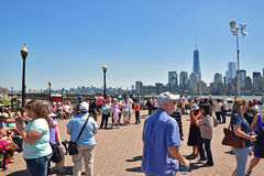 Visitors are waiting at Liberty State Park for Statue Cruises to visit Lady Liberty and Immigration Museum on Ellis Island. Freedom Tower in the background royalty free stock photo