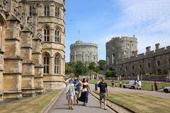 Visitors walk next to St. George`s Chapel in Windsor Castle, UK. WINDSOR, ENGLAND, UK - JULY 7, 2017:  Tourist walk along St George`s Chapel on their way to the Stock Photos