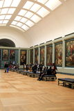 Visitors wandering through rooms filled with masterpieces,The Louvre,Paris,France,2016. Gorgeous masterpieces hanging on walls, with visitors wandering around Stock Image