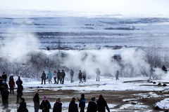 Visitors watching the eruption of a geyser in Iceland Stock Photo