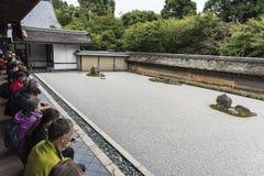 Visitors watching Ryoan-ji dry garden Kyoto Japan stock photo