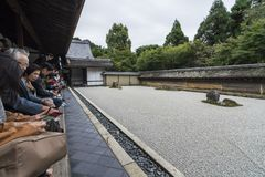 Visitors watching Ryoan-ji dry garden Kyoto Japan stock photography